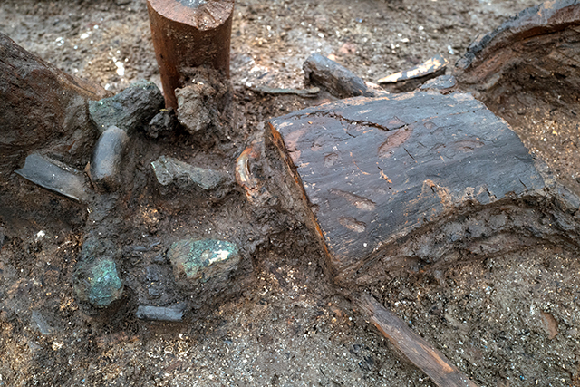 The remains of a wooden bucket that contained scrap bronze associated with Structure 4.