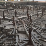 """Quadrant of roundhouse one with the roof still to be excavated. The """"fan"""" shape of the rafters has remained as they sank to the bottom of the river."""